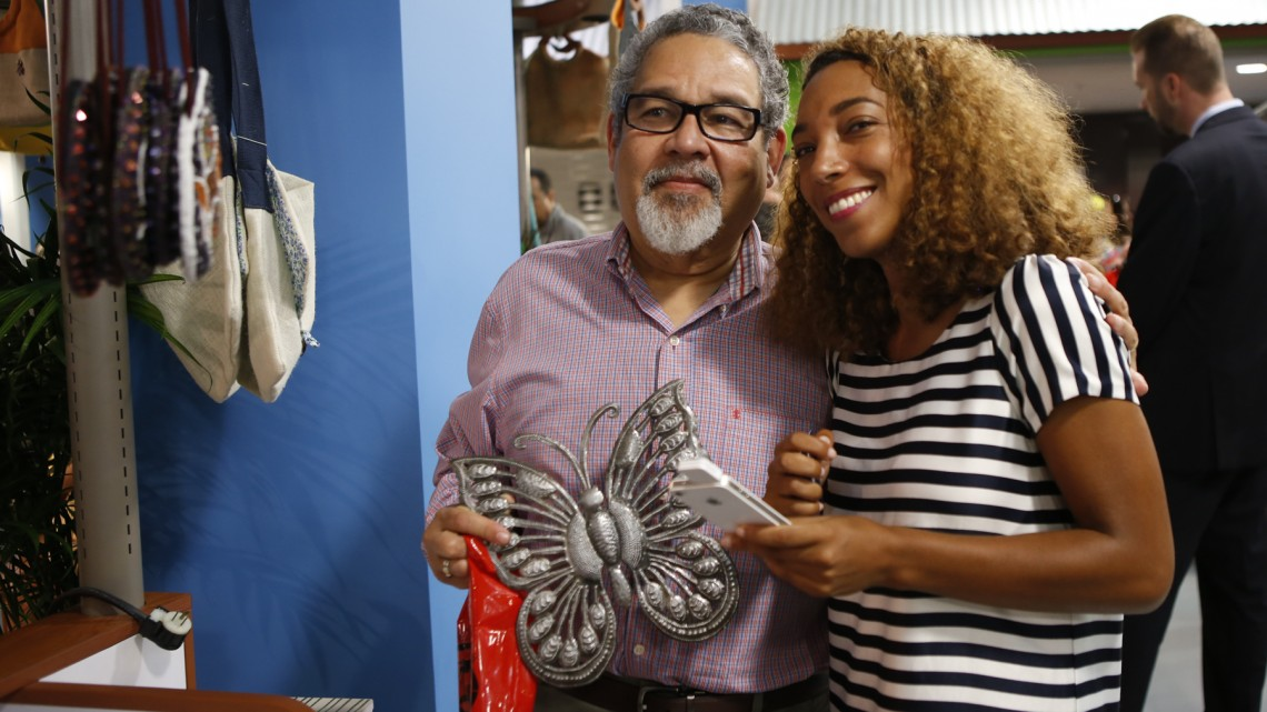 Dr. Michel Dodard, director, Office of Community Health Affairs buys a butterfly from Corail Estime, proprietor of Mango Dore at the opening of the Caribbean Marketplace in Little Haiti Friday.