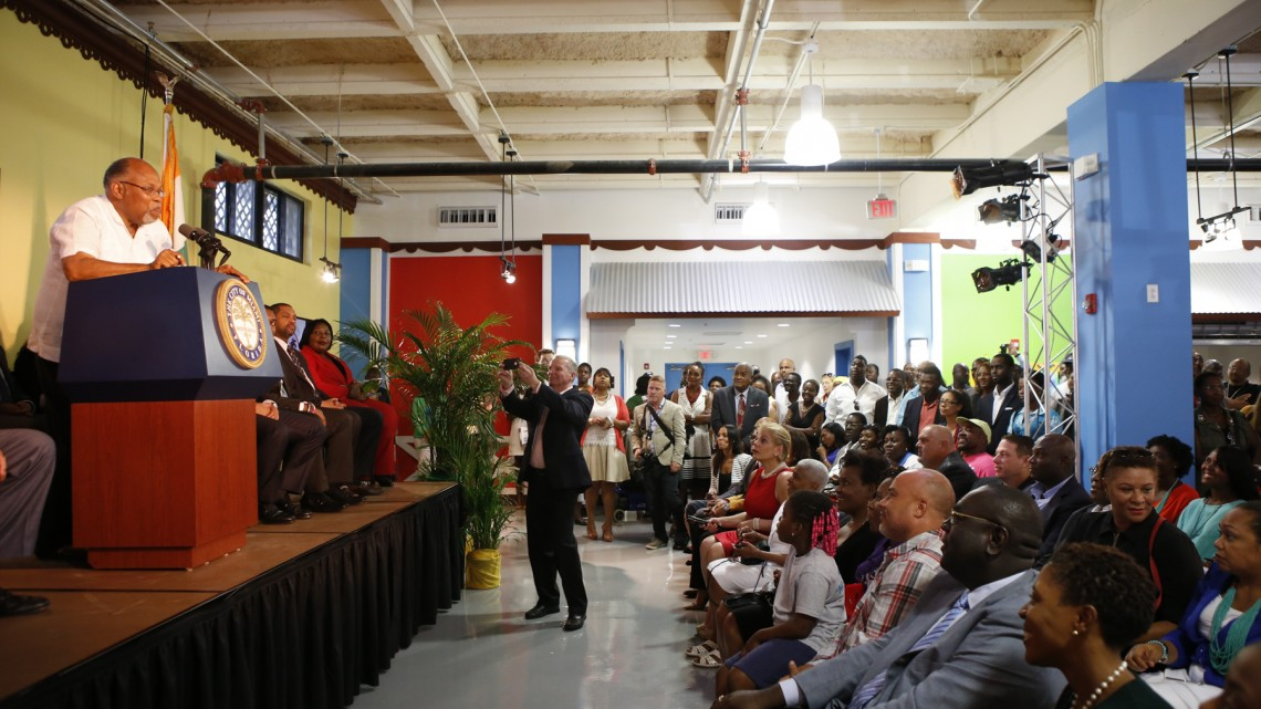 Jean Mapou Denis, an original participant of the Caribbean Marketplace, addresses the audience at the reopening Friday.