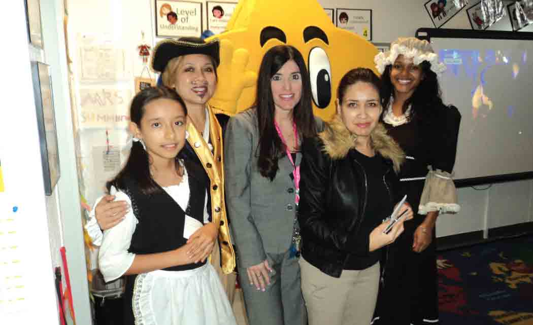 Fifth-grade students at Pembroke Lakes Elementary School recently took an electronic field trip back to colonial times to sing songs, dress in period costumes and watch Colonial Idol, a musical competition modeled after the current-day American Idol. Sponsored by BrightStar Credit Union for 60 Broward County elementary and middle schools, the e-field trips are broadcast online and allow students to interact with actors, ask questions and learn about life in colonial times. The Colonial Williamsburg Foundation in Williamsburg, VA, (www.history.org) which runs the world's largest living history museum dedicated to the study of 18th century American history and culture, provided the curriculum. Participating in Colonial Idol in the photo at right/left/above/below are (left to right) Keyla Jaramillo, a fifth grade student; Marjuree Larin, BrightStar Credit Union; Sandra Shipman, principal, Pembroke Lakes Elementary; Jenny Summerall, teacher, Pembroke Lakes Elementary; and Blaise DaCosta, BrightStar Credit Union​