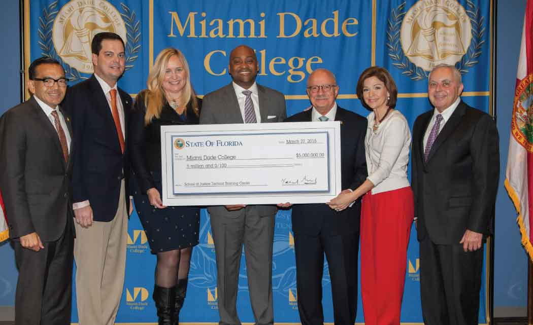 Florida Senator Oscar Braynon II presented the Miami Dade College (MDC) Board of Trustees with a check for $5 million to repair and renovate the gymnasium at MDC North Campus, where as a young man Sen. Braynon played his first game of basketball and attended summer camp. The renovation will include the creation of a tactical training facility for the MDC School of Justice. Holding the check: (L-R) MDC Board of Trustees members Jose K. Fuentes, Bernie Navarro, Marili Cancio, Sen. Braynon, MDC President Dr. Eduardo J. Padrón, Helen Aguirre Ferré, and Armando J. Olivera.