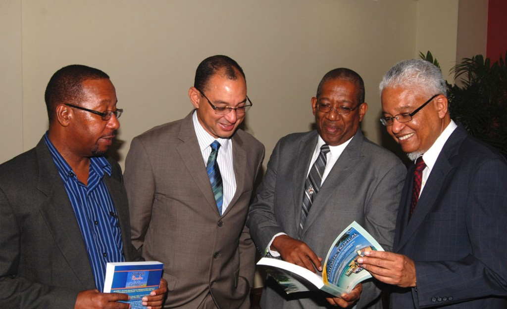 PHOTO COURTESY OF GraceKennedy Foundation L-R: Professor Ian Boxill, (Carlton Alexander Chair in Management), Don Wehby (GK Ltd Group CEO), Professor Dale Webber (James Moss-Solomon Sr Chair in Environmental Management) and Professor E. Nigel Harris glance through the textbook 'Revista de Biologia Tropical', edited by Prof. Dale Webber during the GKF/UWI Chair Press Conference on November 18, 2014 at the Council Room, UWI Regional Headquarters.