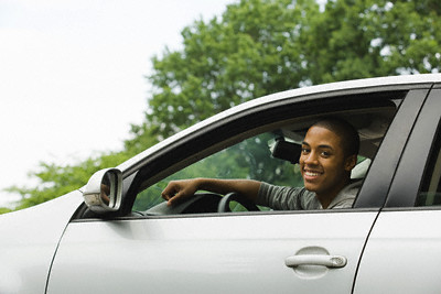 Smiling Young Man Driving --- Image by © Image Source/Corbis