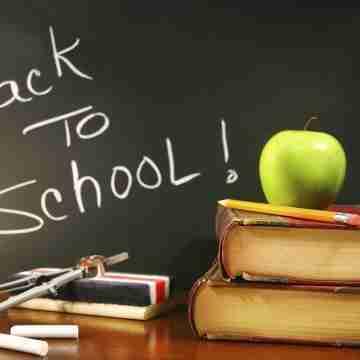 School books with apple on desk