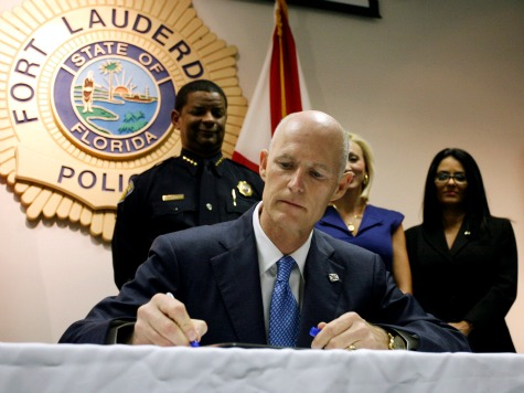 """Gov. Rick Scott signs a new law aimed at controlling the state's """"pill mills"""" by penalizing doctors who overprescribe painkillers, tightening rules for operating pharmacies and authorizing a prescription-drug monitoring database during a ceremony at a Fort Lauderdale, Fla. police station, Friday, June 3, 2011. Florida is considered the epicenter of prescription drug abuse, with pain-management clinics supplying drug dealers and addicts with illicit prescription painkillers. Many of those people come from out of state. (AP Photo/J Pat Carter)"""