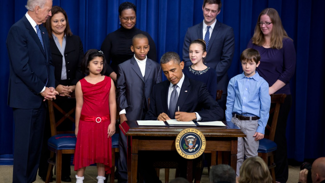 President Barack Obama, with Vice President Joe Biden, signs executive orders initiating 23 separate executive actions, after delivering remarks to unveil new gun control proposals as part of the AdministrationÕs response to the Newtown, Conn. shootings, and other tragedies, in the Eisenhower Executive Office Building, Jan. 16, 2013.  Joining them on stage are children from around the country who wrote the President letters in the wake of the Newtown tragedy expressing their concerns about gun violence and school safety, and their parents. (Official White House Photo by Lawrence Jackson)
