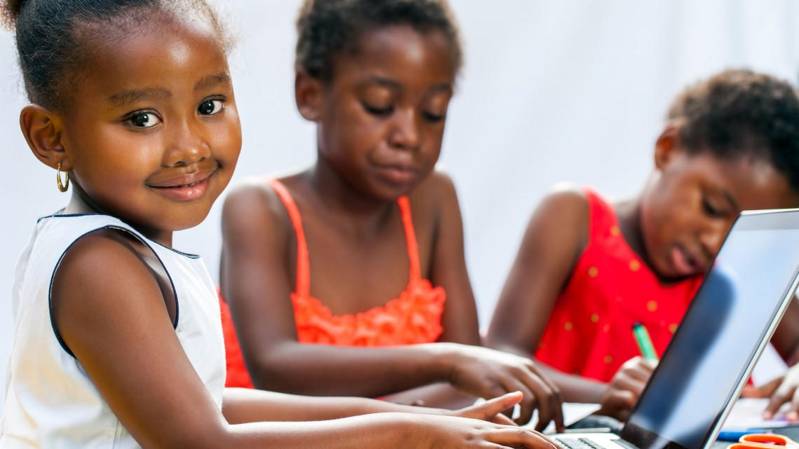 portrait of cute little african girl doing homework on computer with friends at desk.isolated on light background.