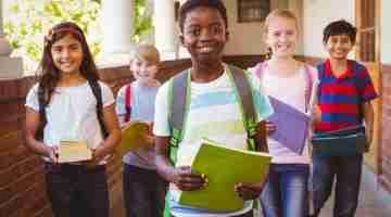 38133398 - portrait of smiling little school kids in school corridor