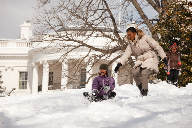 First Lady Michelle Obama with daughters Malia and Sasha sled in the snow on the South Lawn of the White House 3/2/09. Official White House Photo by Pete Souza