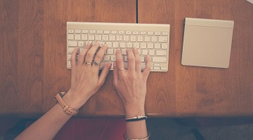 Hands-woman-apple-desk