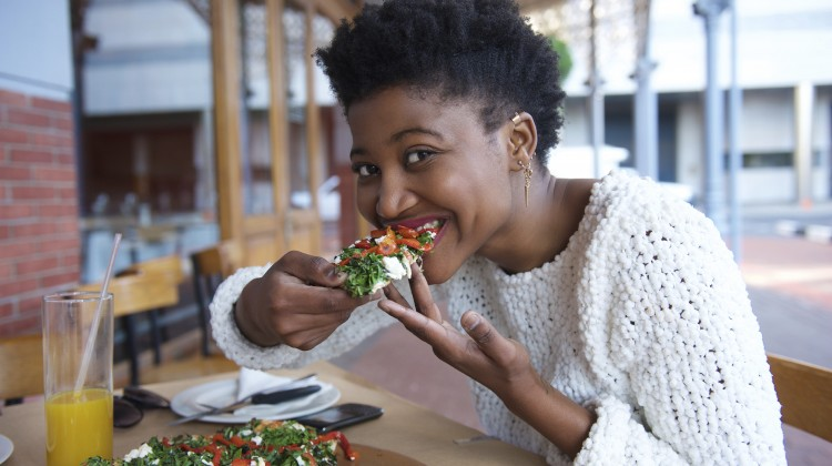 Close up portrait of a young black woman eating vegetarian pizza