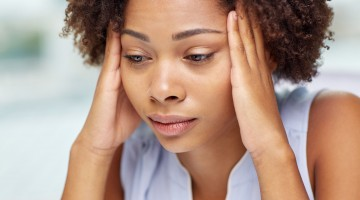 49160602 - people, emotions, stress and health care concept - unhappy african american young woman touching her head and suffering from headache
