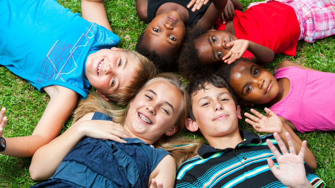 25880110 - diverse multiracial group of kids laying together joining heads.