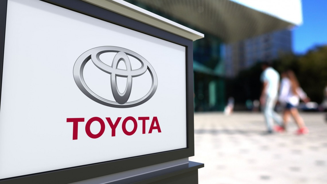 65672927 - street signage board with toyota logo. blurred office center and walking people background. editorial 3d rendering united states