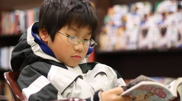 1200px-Young_boy_reading_manga