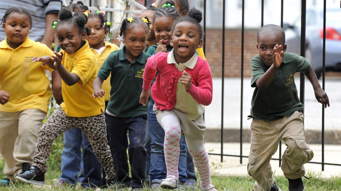 Children at the Little Flowers Child Development Center romp on the playground. Their teachers like to get them outsidein the sunshine to exercise, which helps them to focus later in the classroom.
