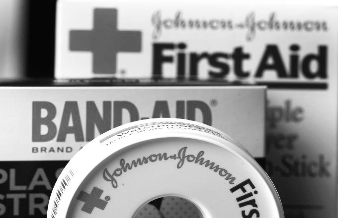 In this Monday, July 16, 2012, photo,  Johnson & Johnson products are displayed in Orlando, Fla. Johnson & Johnson, a health care giant that is struggling with tougher market conditions, ongoing manufacturing problems and other issues, lowered its profit forecast for the year after posting second-quarter net income that dropped by half. The maker of Band-Aids, medical devices and prescription drugs whose iconic image has been tarnished by legal and manufacturing lapses on Tuesday, July 17, 2012 noted some positive signs. (AP Photo/John Raoux)